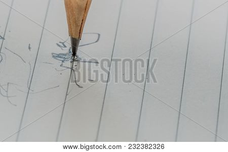 Closeup Of Pencil Tip With Crack In Wood Standing Vertically On Lined White Paper With Scribbles In