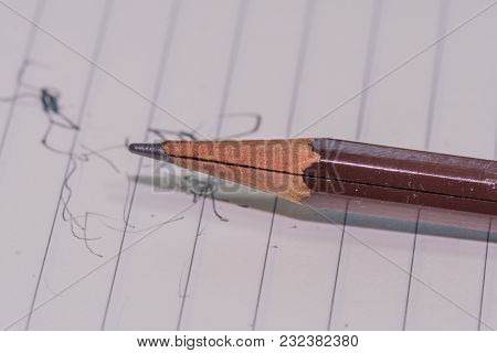 Closeup Of Broken Brown Wooden Pencil With Creak In Wood Laying On Lined White Paper With Scribbles