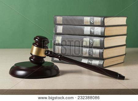 Law Concept. Stack Of Books With Wooden Judge's Gavel On Table In A Courtroom Or Enforcement Office.