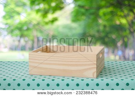 Empty Wooden Box On Table With Green Polka Dot Tablecloth Over Blur Tree With Bokeh Light Background