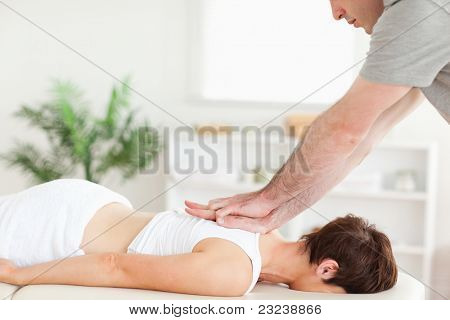 A masseur is massaging a female customer's back in his surgery
