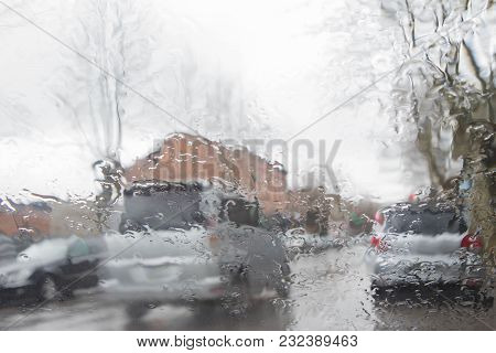 Road View Through Car Window With Rain Drops. Street Bokeh Lights Out Of Focus. Rainy Day In The Cit