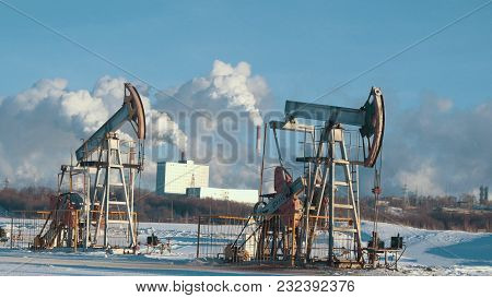 Operating Pumps For Crude Oil Production Against The Background Of Petrochemical Plant, Petroleum In