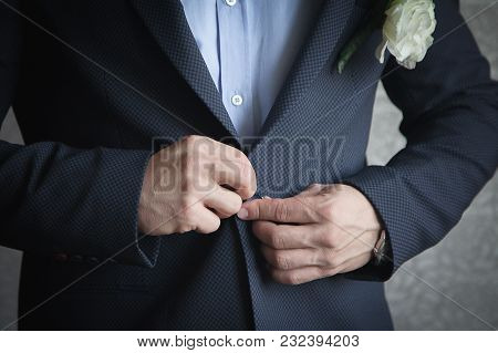 A Man In A Blue Shirt Is Buttoning His Jacket.