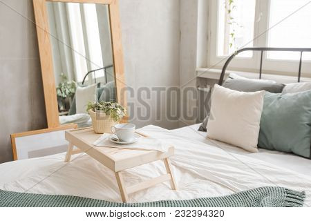 Interior Shot Of Made Bed In Daylight With Wooden Table Served On Top With Cup Of Coffee.
