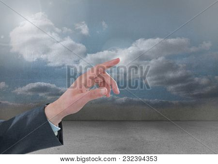 Digital composite of Hand Touching air of cloudy sky
