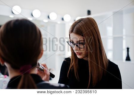 Make up artist work in her beauty visage studio salon. Woman applying by professional make up master. Beauty club concept. poster
