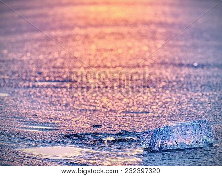 Ice Piece In Selective Focus Photo. Detail View Into Deep Clefts And Frozen Bubbles In Broken Ice.