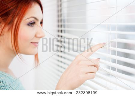 Woman At The Window Looking Through The Jalousie At The Kitchen