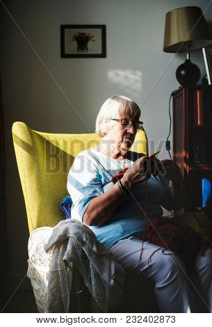 Senior woman knitting for hobby at home