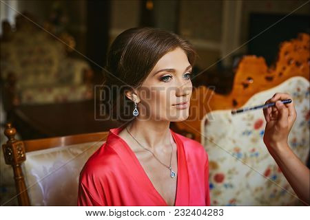Makeup Artist Applies Makeup For Beautiful Brunette Young Woman With Blue Eyes, Wearing In Peach Pei