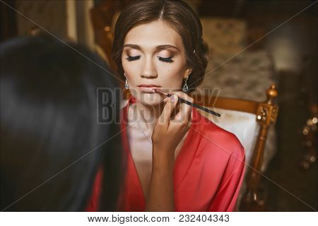 Makeup Artist Applies Makeup For Beautiful Brunette Young Woman With Sexy Lips And Closed Eyes, Wear
