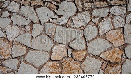 Texture. Background. Masonry Light Rubble Stone. Dark Seam. Different Size Of Stones. Inhomogeneous