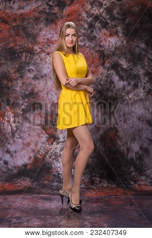 Young Blond Woman In Yellow Dress On Marble Multicolored Background. Model Test.