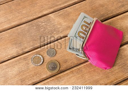 A Hundred Dollar Bill In My Wallet And Coins On A Wooden Table . On Wooden Background .