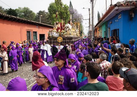 Antigua, Guatemala: March 18 2018: Visitors Watching Purple Robed Men Carrying A Float With Christ A