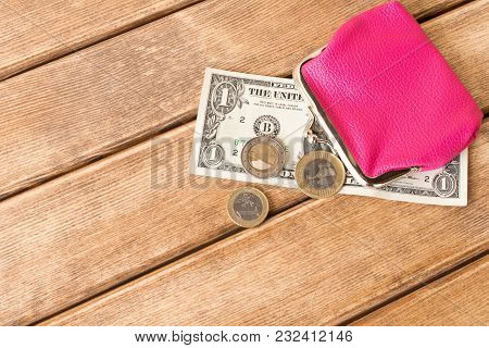 One Dollar Bill In My Wallet And Coins On A Wooden Table . On Wooden Background .