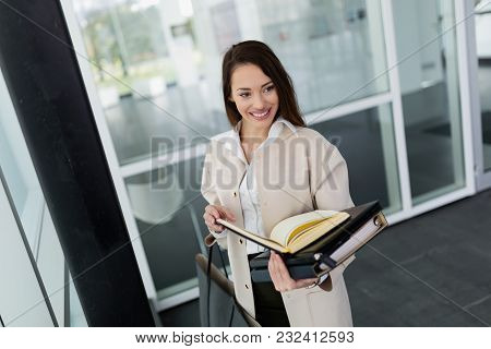 Attractive And Beautiful Businesswoman Holding Files In Hands At Office