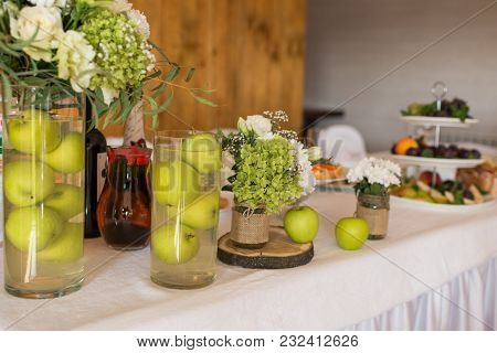 Rustic Flower Arrangement With White Flowers And Greenery In A Glass Vase With Water And Apples At A