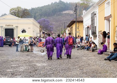 Antigua, Guatemala: March 18 2018: Three Purple Robbed Men With Incense Smoker On The Cobbled Street