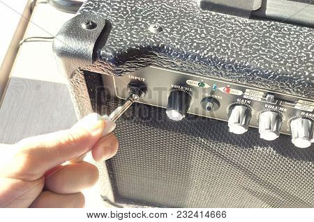 Cord In The Hand Inserts Into A Guitar Amp Sunlight