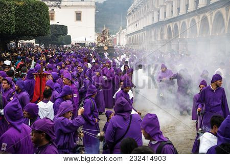 Antigua, Guatemala: March 18 2018: Purple Robed Men Use Incense Smoker In Front Of Float At The Proc
