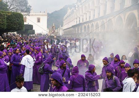 Antigua, Guatemala: March 18 2018: Purple Robed Men And Incense Smoke At The Procession San Bartolom