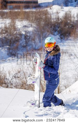 Image Of Female Athlete Wearing Helmet With Snowboard Standing In Park On Winter Day