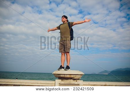 Male Runner Relaxing After Training While Standing On Stone Rock With Hands Raised Against Sky Backg