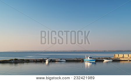 Sea Lagoon In Windless Conditions In Summer At Sunset. Fishing Boats Near The Stone Peer.