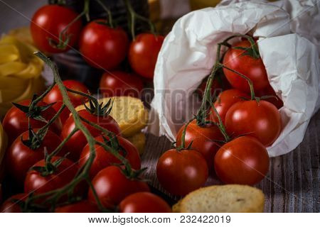 Red Cherry Tomatoes In Paper Bag On Vintage Wooden Table With Tagliatelle And Bruschetta