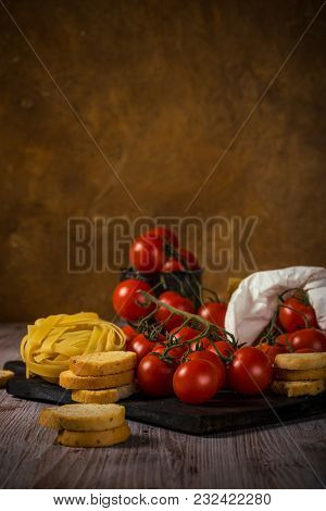 Small Red Cherry Tomatoes On Several Twigs With Bruschetta