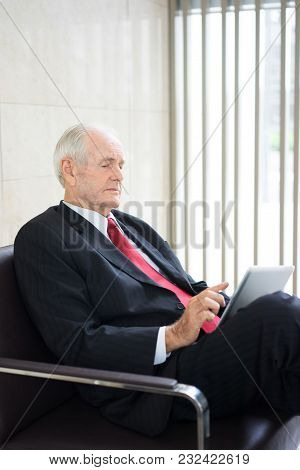 Portrait Of Confident Senior Caucasian Businessman Wearing Formal Suit Sitting In Armchair And Worki