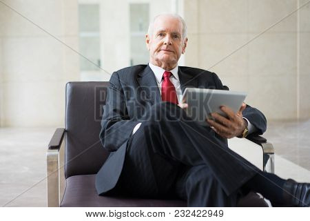 Portrait Of Confident Senior Caucasian Mentor Wearing Formal Suit Sitting In Armchair With Touchpad.