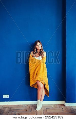 Happy Girl Wearing A Knitted Yellow Sweater Over Blue Background
