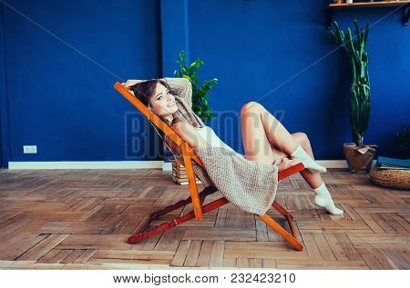 Young Woman At Home Sitting On Modern Chair Relaxing In Her Living Room