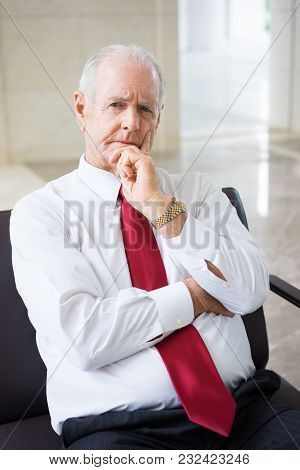 Portrait Of Pensive Or Doubtful Senior Caucasian Executive Wearing Shirt And Tie Sitting In Armchair