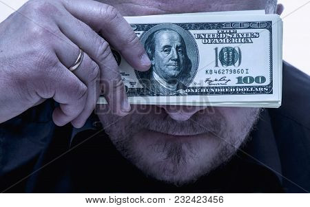 The Eyes Of Adult Man Close The Money As A Symbol Of A Desire To Be Successful And To Be Rich. (purp