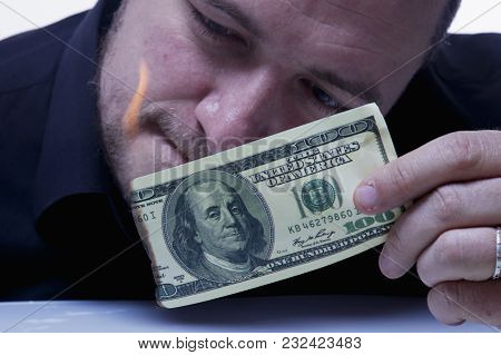 Money Is Not The Best Method Of  Motivation. Close Up A Man Burns A Hundred Dollar Bill.