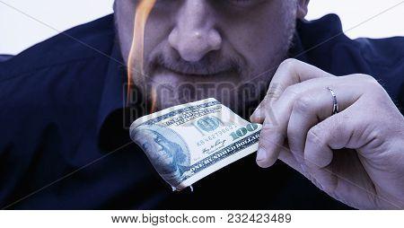 Money Is Not The Best  Motivation. Close Up A Man Burns A Hundred Dollar Bill.