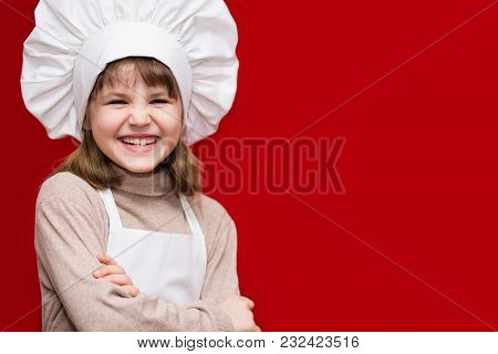 Happy Little Girl In Chef Uniform Isolated On Red. Kid Chef. Cooking Process Concept