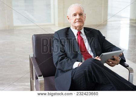 Portrait Of Serious Senior Caucasian Expert Wearing Formal Suit Sitting In Armchair With Touchpad Wa