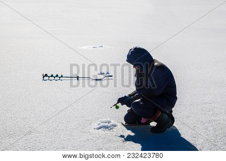 Fisherman Holding A Fishing Rod For Winter Fishing