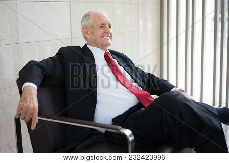 Portrait Of Successful Senior Caucasian Leader Wearing Formal Suit Sitting In Armchair And Smiling I