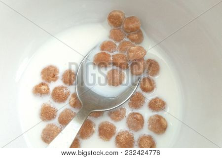 Morning Breakfast With Milk And Wheat Balls On A Spoon