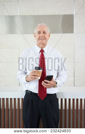 Portrait Of Senior Caucasian Businessman Wearing Shirt And Tie Standing With Coffee And Mobile Phone