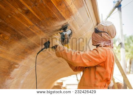 Abu Dhabi, Uae - March 27, 2005: An Unidentified Workman Renovating A Traditional Wooden Dhow At The