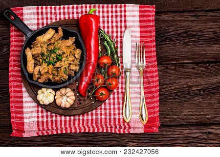 Top View Frying Pan With Roasted Pork And Garlic, Pepper, Rosemary And Tomatoes On Tablecloth. Selec