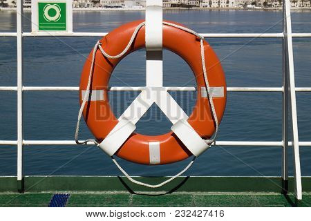 Orange Lifebuoy On Deck Railing Of Passenger Ship