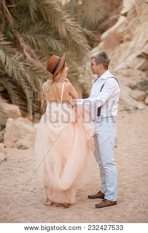 Bride And Groom Stand In Canyon On Sand Against Backdrop Of Palm Trees And Rocks.